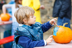 Little kid boy painting with colors on pumpkin Royalty Free Stock Photo