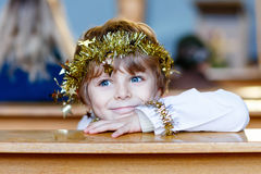 Little kid boy playing an angel of Christmas story in church. Beautiful little kid boy playing an angel in Christmas story in a church. Happy adorable blond Stock Photo