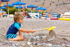 Little kid boy playing on beach with stones Stock Image
