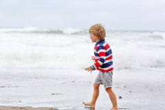 Little kid boy playing on beach on stormy day Stock Images