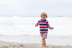 Little kid boy playing on beach on stormy day Royalty Free Stock Photo