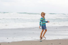 Little kid boy playing on beach on stormy day Stock Photography