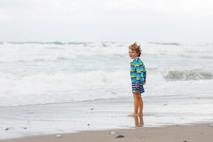 Little kid boy playing on beach on stormy day Royalty Free Stock Photography