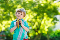 Little kid boy playing with car toy, outdoors Stock Photo