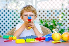 Little kid boy playing with colorful plastic blocks Stock Photos