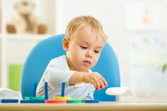 Little kid boy playing with educational toys Stock Images