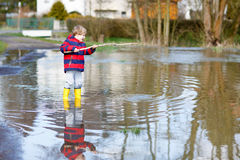 Little kid boy playing paper ship puddle stock photos for Puddle of fish