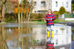 Little kid boy playing with fishing rod by puddle Royalty Free Stock Image