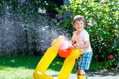 Little kid boy playing with a garden hose. Adorable little kid boy playing with a garden hose on hot and sunny summer day. Child having fun outdoors. Funny stock photos
