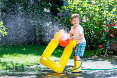 Little kid boy playing with a garden hose. Adorable little kid boy playing with a garden hose on hot and sunny summer day. Child having fun outdoors. Funny stock photography