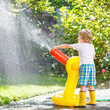 Little kid boy playing with a garden hose. Adorable little kid boy playing with a garden hose on hot and playing with water outdoors. Funny leisure for children royalty free stock photography