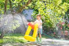 Little kid boy playing with a garden hose. Funny little kid boy playing with a garden hose on hot and sunny summer day. Child having fun outdoors. Funny outdoors royalty free stock image