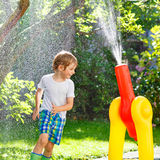 Little kid boy playing with a garden hose and water. Active preschool kid boy playing and splashing with a garden hose on hot and sunny summer day. Child having stock images