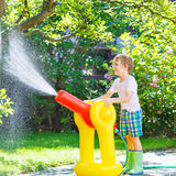 Little kid boy playing  with a garden hose and water Stock Images