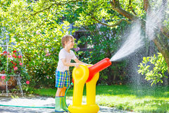 Little kid boy playing  with a garden hose and water Royalty Free Stock Photo