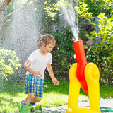 Little kid boy playing with a garden hose and water. Happy little kid boy playing and splashing with a garden hose on hot and sunny summer day. Child having fun stock images