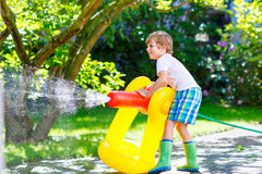 Little kid boy playing with a garden hose water sprinkler. Funny little kid boy playing with a garden hose sprinkler on hot and sunny summer day. Child having royalty free stock photo
