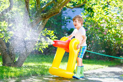 Little kid boy playing with a garden hose water sprinkler Stock Photo
