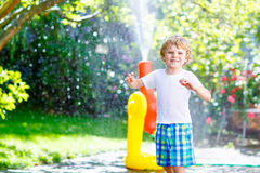 Little kid boy playing with a garden hose water sprinkler Royalty Free Stock Images