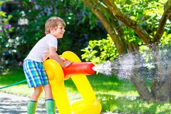 Little kid boy playing with a garden hose water sprinkler Royalty Free Stock Photo