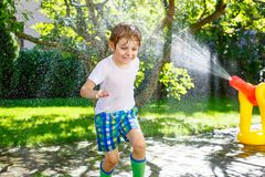 Little kid boy playing with a garden hose water sprinkler Royalty Free Stock Photography