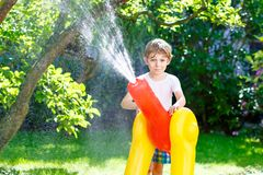 Little kid boy playing with a garden hose water sprinkler Stock Images
