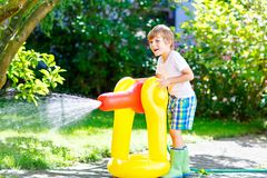 Little kid boy playing with a garden hose water sprinkler Royalty Free Stock Image