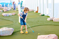 Little kid boy playing mini golf on a cruise liner. Royalty Free Stock Images
