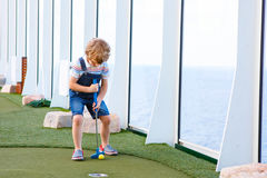 Little kid boy playing mini golf on a cruise liner. Stock Image