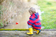 Little kid boy playing with paper ship by creek. Happy little kid boy in yellow rain boots playing with paper ship by a creek on spring or autumn day. Active stock images