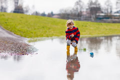 Little kid boy playing with paper ship by puddle. Happy little kid boy in rain boots playing with paper ship by a puddle on warm spring day. Active leisure for royalty free stock photo