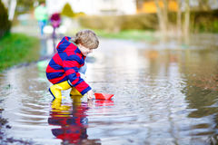 Little kid boy playing with paper ship by puddle. Happy little kid boy in yellow rain boots playing with paper ship by a puddle on spring or autumn day. Active royalty free stock image