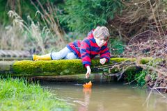 Little kid boy playing with paper ship by puddle stock photo