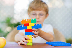 Little kid boy playing with plastic blocks Stock Photos