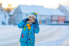 Little kid boy playing with snow in winter. Cute little kid boy in colorful winter clothes having fun, outdoors during snowfall. Active outdoors leisure with Stock Photo