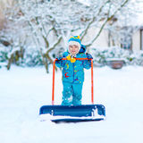 Little kid boy playing with snow in winter. Cute little kid boy in colorful winter clothes having fun with snow shovel, outdoors during snowfall. Active outdoors Royalty Free Stock Images