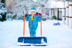 Little kid boy playing with snow in winter. Cute little kid boy in colorful winter clothes having fun with snow shovel, outdoors during snowfall. Active outdoors Royalty Free Stock Photo