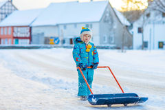 Little kid boy playing with snow in winter. Cute little kid boy in colorful winter clothes having fun with snow shovel, outdoors during snowfall. Active outdoors Stock Photography
