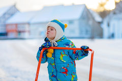 Little kid boy playing with snow in winter. Cute little kid boy in colorful winter clothes having fun with snow shovel, outdoors during snowfall. Active outdoors Royalty Free Stock Image
