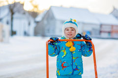 Little kid boy playing with snow in winter. Cute little kid boy in colorful winter clothes having fun with snow shovel, outdoors during snowfall. Active outdoors Royalty Free Stock Photos