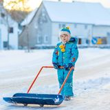 Little kid boy playing with snow in winter, outdoors. Cute little kid boy in colorful winter clothes having fun with snow shovel, outdoors during snowfall Stock Images
