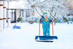 Little kid boy playing with snow in winter, outdoors. Cute little kid boy in colorful winter clothes having fun with snow shovel, outdoors during snowfall Royalty Free Stock Image