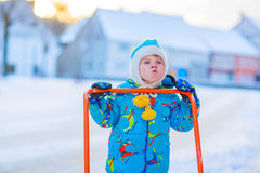 Little kid boy playing with snow in winter, outdoors. Cute little kid boy in colorful winter clothes having fun with snow shovel, outdoors during snowfall Stock Image