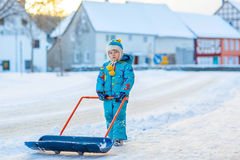 Little kid boy playing with snow in winter, outdoors. Cute little kid boy in colorful winter clothes having fun with snow shovel, outdoors during snowfall Royalty Free Stock Photo