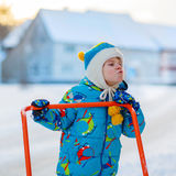Little kid boy playing with snow in winter, outdoors. Cute little kid boy in colorful winter clothes having fun with snow shovel, outdoors during snowfall Stock Photo