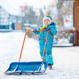 Little kid boy playing with snow in winter, outdoors. Cute little kid boy in colorful winter clothes having fun with snow shovel, outdoors during snowfall Royalty Free Stock Photos