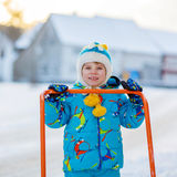 Little kid boy playing with snow in winter, outdoors. Cute little kid boy in colorful winter clothes having fun with snow shovel, outdoors during snowfall Royalty Free Stock Images