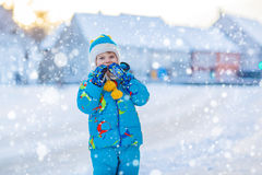 Little kid boy playing with snow in winter, outdoors. Cute little kid boy in colorful winter clothes having fun, outdoors during snowfall. Active outdoors Stock Photos