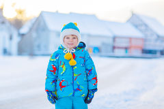 Little kid boy playing with snow in winter, outdoors. Cute little kid boy in colorful winter clothes having fun, outdoors during snowfall. Active outdoors Royalty Free Stock Photography