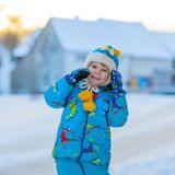 Little kid boy playing with snow in winter, outdoors. Cute little kid boy in colorful winter clothes having fun, outdoors during snowfall. Active outdoors Stock Photography